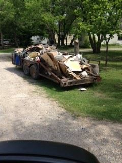 Car trailer with piles of trash not bound together